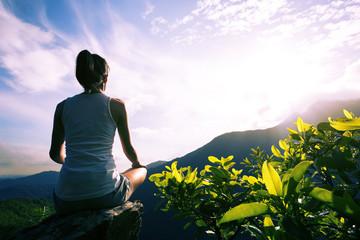 Young yoga woman at sunrise mountain peak cliff edge