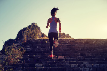 woman trail runner running upstairs on the great wall top of mountain