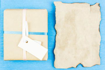 Gift box made of Kraft paper and blank parchment for your text on a blue background. Congratulations on the holiday.