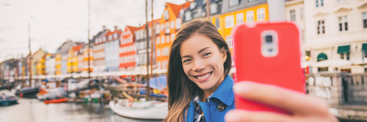 Selfie tourist girl taking photo with phone at Copenhagen Nyhavn, famous Europe tourism attraction. Asian woman at waterfront water canal in Kobenhavn, Denmark, Scandinavia. Banner panorama.