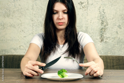 Sad Young Brunette Woman Dealing With Anorexia Nervosa Or Bulimia Having Small Green Vegetable On Plate