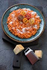 Turquoise plate with tomato risotto and parmesan on a black wooden serving board, vertical shot
