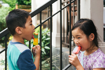 Asian american brother and sister eating popsicles facing each other on porch steps