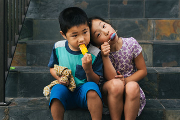 Chinese American girl leaning her head on brother's shoulder while they eat popsicles outside