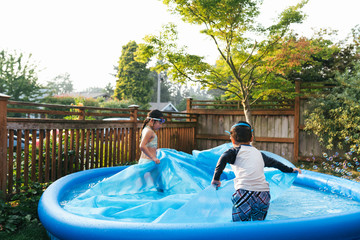 Asian girl and boy spreading cover over inflatable outdoor pool