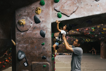 Little boy bouldering in indoor climbing gym with father's help