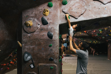Asian American father helping little boy reach for hold while bouldering