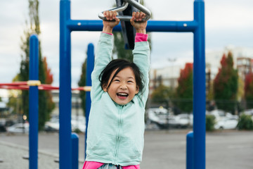 Chinese American girl with large smile rides zip line on playground structure