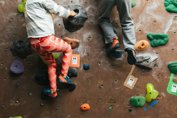 Twin siblings climbing on rock wall next to each other indoors