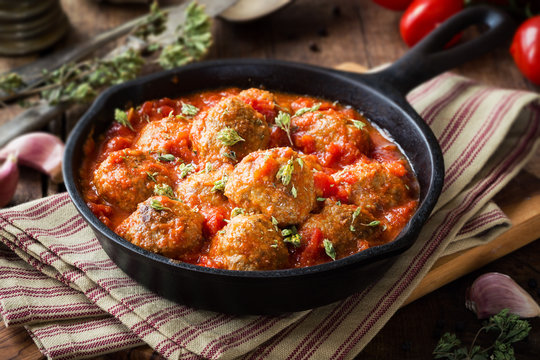 Meatballs in tomato sauce with dried oregano in a rustic vintage cast iron skillet