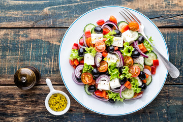 Greek salad of fresh cucumber, tomato, sweet pepper, lettuce, red onion, feta cheese and olives with olive oil. Healthy food, top view Fototapete