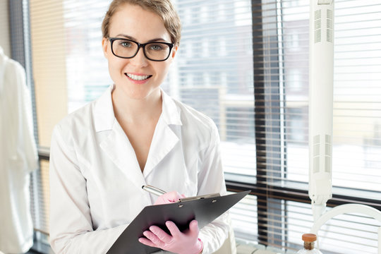 Waist-up portrait of pretty young doctor wearing white coat and rubber gloves distracted from taking notes in order to pose for photography