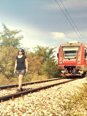 Woman listening music on railway track, earphones, train coming