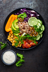 Buddha bowl dish with brown rice, avocado, pepper, tomato, cucumber, red cabbage, chickpea, fresh lettuce salad and walnuts. Healthy vegetarian eating, super food. Top view