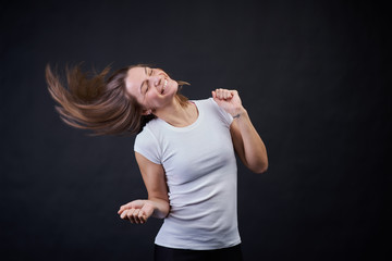 Studio portrait on a black background of a young athletic girl dancing and having fun.