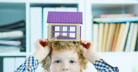 Little Caucasian curly boy holding the plastic figure of houseover his head close-up. Family home security concept.