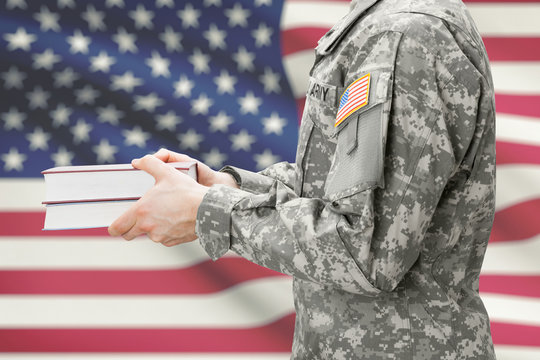 USA army soldier holding books in his hands