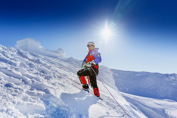 Foto op Aluminium Alpinisme Equipped climber ascent by snowy slope with climbing rope on the top of peak in snowy alpine mountains. Life guard professional man on the work in high mountains. Action in hard conditions scene.