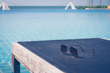 Summer Vacation and Holiday Concept :Sunglasses put on wooden daybed in swimming pool with seascape view in background.