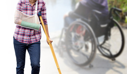Injured woman standing with green cast on arm and arm sling using wood crutches isolated on blurred background seniors woman sitting in wheelchair, clipping path included, insurance concept