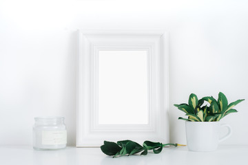 White frame desktop with yellow-green leaves in small coffee cup and candle