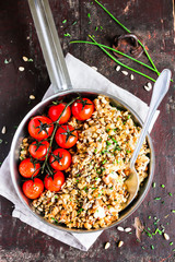 Savory crumble with white fish cod and mixed seeds served with roasted cherry tomatoes in a pan on a wooden table, selective focus