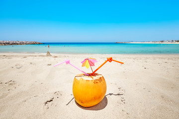 Coconut with colorful umbrella and two straws on a beach, summer holiday concept, selective focus.