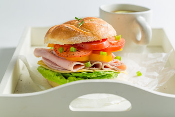 Tasty sandwich with cheese, ham and tea