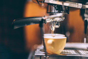 professional coffee machine preparing fresh coffee and pouring into cups at restaurant, bar or pub. Barista life details