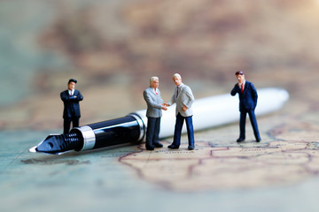 Miniature people: Businessman handshake on the world map with pen. Commitment, agreement,...