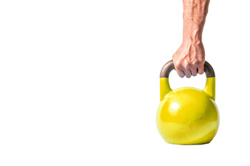Strong muscular man hand with muscles holding yellow heavy kettlebell partially isolated on white background