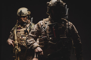 soldiers or private military contractors holding rifle. Image on a black background. war, army, weapon, technology and people concept