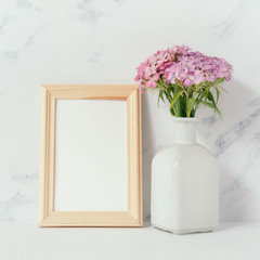 Home office desk with photo frame mock up, bouquet of pink phloxes in front of pale marble background. Social media concept
