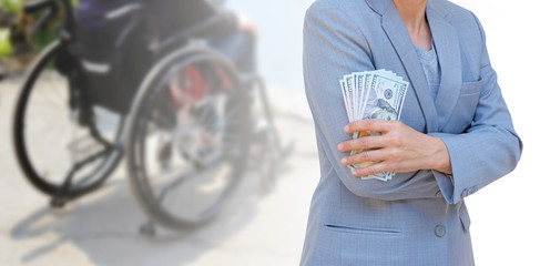 Business woman hand holding American dollar currency isolated on blurred seniors woman sitting in wheelchair, health care cost concept