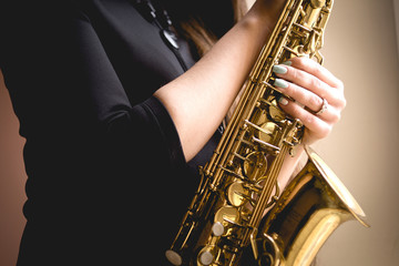 gold saxophone in the hands of girl in black