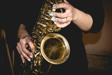 gold saxophone in the hands of girl