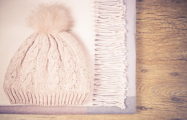 Warm winter knitted clothes on a wooden background.