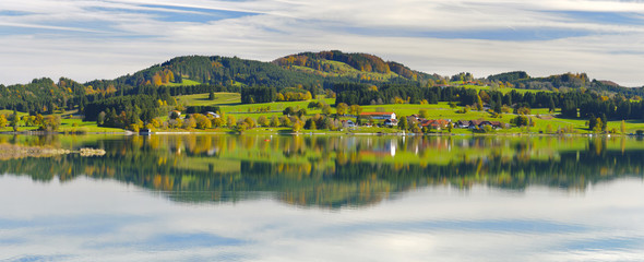 panoramic landscape in region Allgaeu with alps mountain range mirroring symmetric in lake Wall mural
