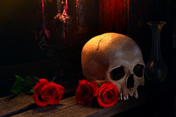 A human skull, red roses, candles on the wooden table. Dark atmosphere. Gothic concept. Vanitas, death