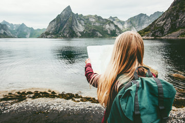 Tourist woman with map sightseeing Lofoten islands in Norway Travel lifestyle concept adventure outdoor summer vacations
