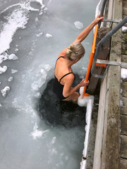 Nice blonde woman descends into hole in the ice in the water for cold winter bathing