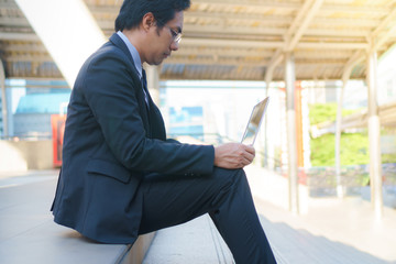 Businessman sitting on the footsteps with laptop