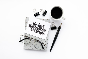 Minimal composition with notepad, calligraphic pen, glasses, mug of coffee, black paper clamps on a white background. Card with quote - the best things in life are simple