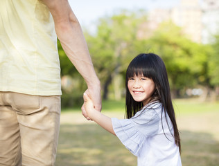 father holds the hand of little girl