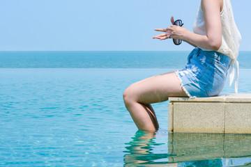 Woman sitting with foot soak in swimming pool
