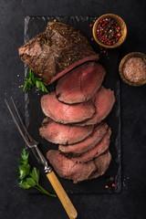 sliced  roast beef with salt and pepper on slate board