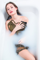 Beautiful young model girl in golden dress in bath, glamour, relaxing, joy, rejuvenation, treatment