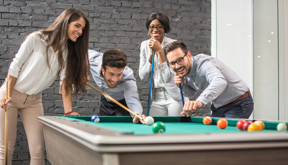 Cheerful business people playing billiards during office break.