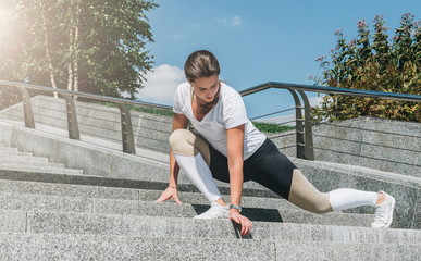 Sunny summer day. Young woman in sportswear doing stretching exercises outdoor. Girl doing warm-up on steps before training. Exercise in street, sports exercises, workout. On background green trees.