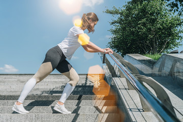 Sunny summer day. Young woman in sportswear doing stretching exercises outdoor. Girl doing warm-up on steps before training. Exercise in street, sports exercises, workout. On background blue sky.